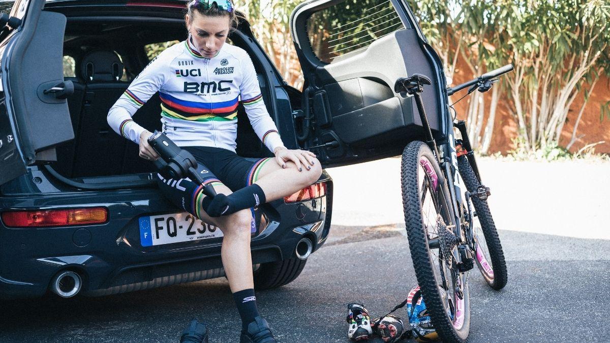 Campeã do Mundo XCO Pauline Ferrand Prevot a utilizar a pistola massajadora Compex Fixx 2.0 no final do treino com a bicicleta BMC