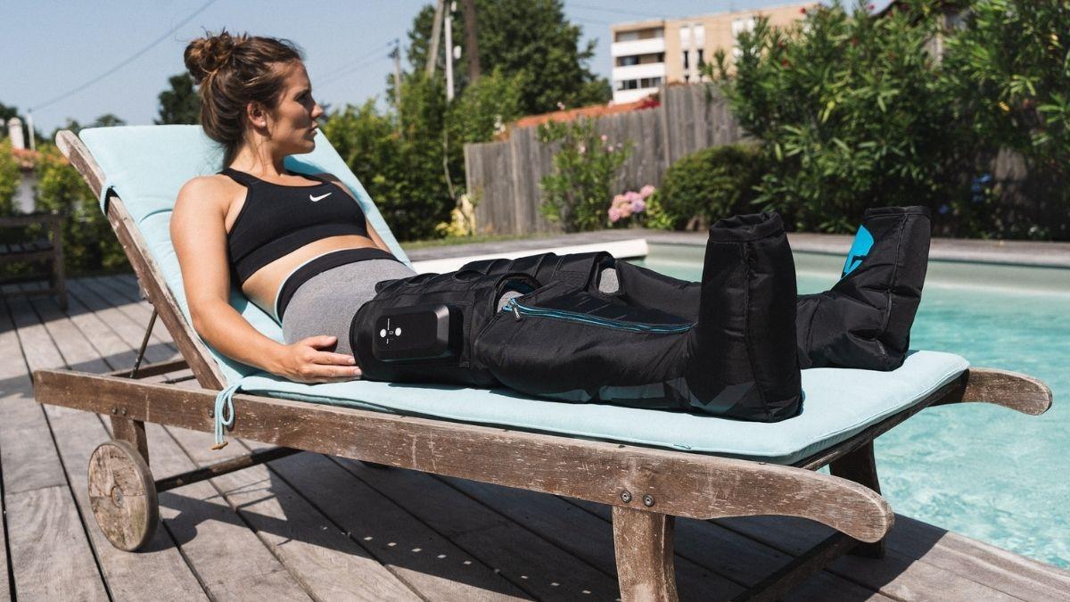 Botas de pressoterapia sem fios Compex Ayre em utilização junto a uma piscina